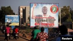 "People ride motorcycles past a billboard for presidential candidate Benewende Sankara in Ouagadougou, Burkina Faso, Nov. 28, 2015. The billboard reads, ""Vote Benewende Sankara, the insurgents' candidate."""