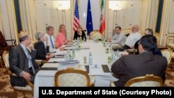 U.S. Secretary of State John Kerry, third from left, and Iranian Foreign Minister Mohammad Javad Zarif, third from right, meet with other officials at an evening session to discuss the nuclear negoatiations in Vienna, Austria, July 11, 2015.