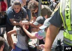 People receive first-aid after a car accident ran into a crowd of protesters in Charlottesville, VA, Aug. 12, 2017.