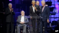 Former President Barack Obama, speaks as fellow former Presidents, from left, Jimmy Carter, George H.W. Bush, George W. Bush, and Bill Clinton look on during a hurricanes relief concert in College Station, Texas, Oct. 21, 2017.
