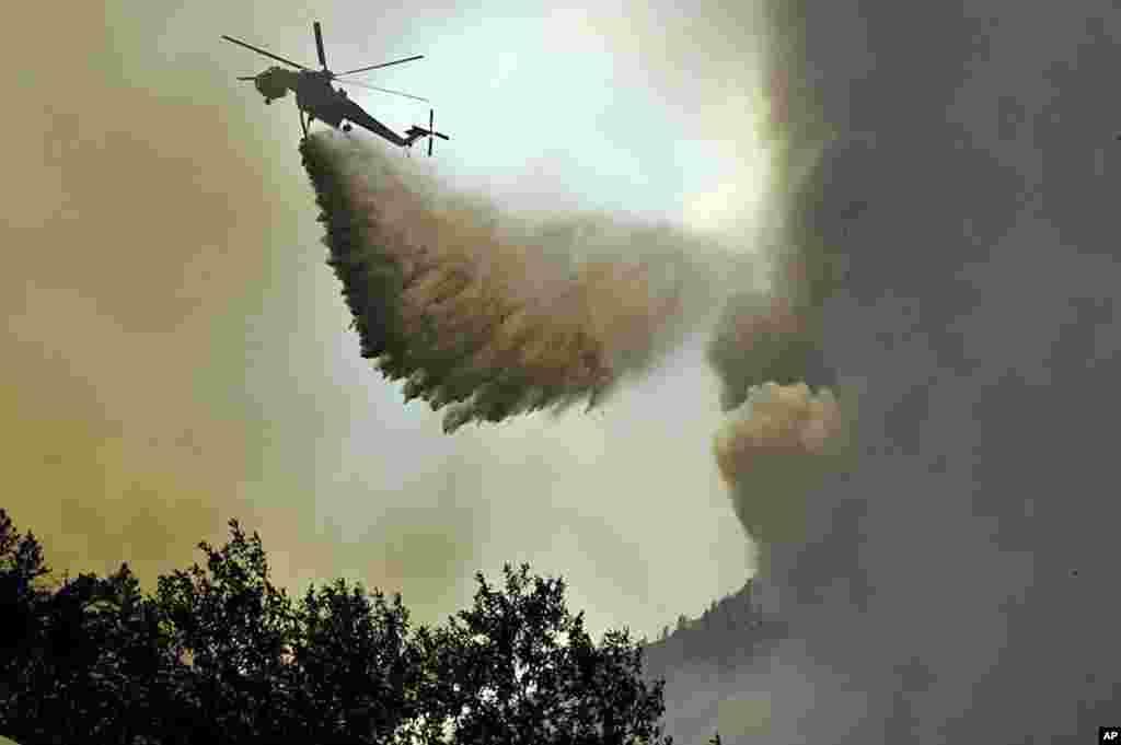 Máy bay trực thăng thả một khối nước bên trên đám cháy rừng High Park.