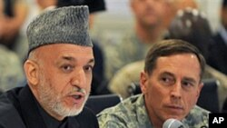 Afghan President Hamid Karzai, left, talks alongside General David Petraeus, U.S. and NATO commander in Afghanistan, at Kabul International Airport (FILE).