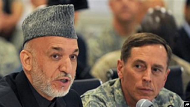 Afghan President Hamid Karzai, left, talks alongside General David Petraeus, U.S. and NATO commander in Afghanistan, at Kabul International Airport (FILE).