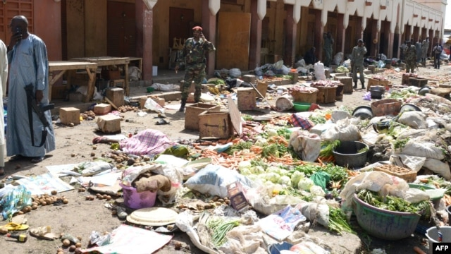 FILE - Soldiers stand guard at a market in N'Djamena following a suicide bomb attack on July 11, 2015.