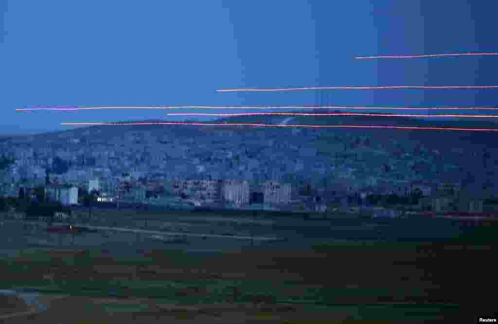 Bullets cross the sky over the Syrian town of Kobani, as seen from the Mursitpinar crossing on the Turkish-Syrian border in the southeastern town of Suruc in Sanliurfa province.