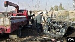 Polisi Afghanistan memeriksa bom pinggir jalan yang menewaskan Gubernur di Kandahar, 15 Juni 2010.