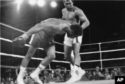 In this Oct. 30, 1974, file photo, challenger Muhammad Ali watches as defending world champion George Foreman goes down to the canvas in the eighth round of their WBA/WBC championship match in Kinshasa, Zaire.