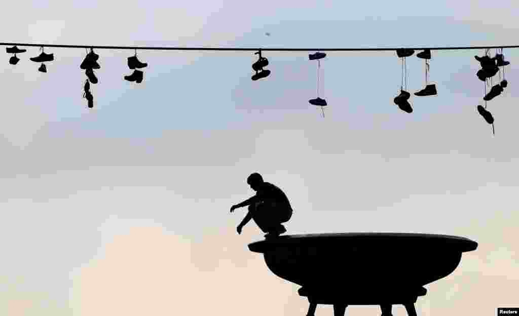 Shoes hang from a power line as a man balances on a statue in a park in Prague, Czech Republic.