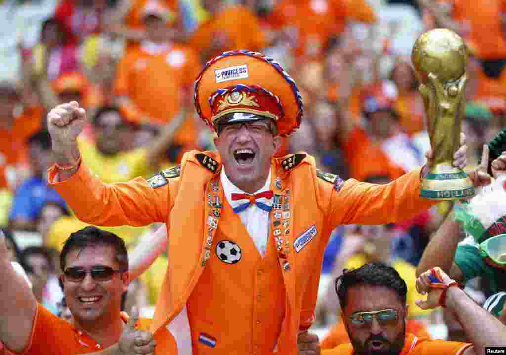 A fan of the Netherlands holding a mock World Cup trophy cheers before the start of the 2014 World Cup round of 16 game between Netherlands and Mexico at Castelao arena in Fortaleza, Brazil.