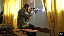 敘利亞的反叛者的於2月22日在霍姆斯省代爾巴勒貝附近的一所社區學校的教室內,利用他的步槍瞄準目標物。