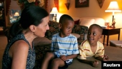 一位美国妇女与她领养的两名在外国出生的孩子。(资料照片)