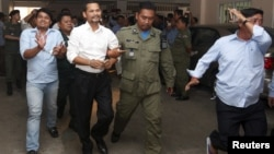 Meach Sovannara (center L), a member of the Cambodia National Rescue Party (CNRP), and a supporter of CNRP (L), are escorted by Cambodian police officers at the Phnom Penh Municipal Court, July 21, 2015.