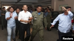 FILE - Meach Sovannara, center left, of the Cambodia National Rescue Party (CNRP) and a CNRP supporter, left, are escorted by police at a Phnom Penh court after 11 CNRP members were sentenced in connection with the Freedom Park protests, July 21, 2015.