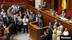 Parliament members surround Oleh Tyahnybok (C), leader of the Svoboda (Freedom) Party, as he delivers a speech at the rostrum during a session in Kyiv July 24, 2014.