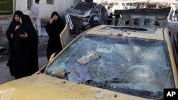 Warga setempat melewati tempat meledaknya bom pinggir jalan di kota Hillah, Irak. (Foto: AP)