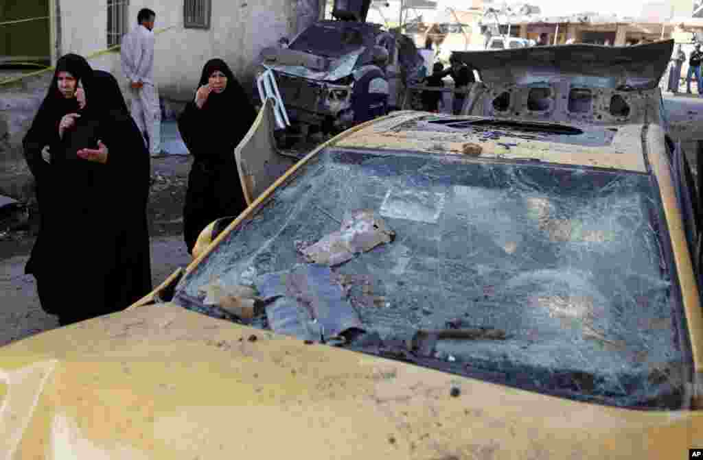 Iraqi women walk through the scene of an explosion in a busy commercial area in Hillah, Iraq, November 29, 2012.