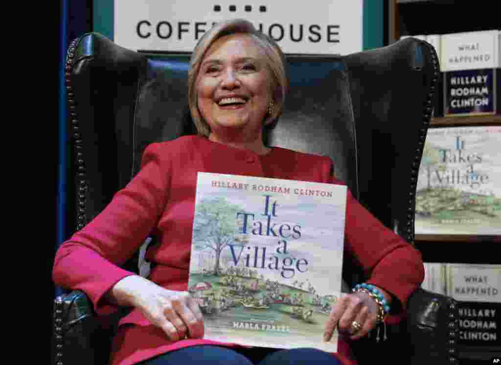 Hillary Clinton, tient son livre It Takes A Village lors de la présentation de son nouveau livre What Happened au Warner Theatre, Washington, 18 septembre 2017.