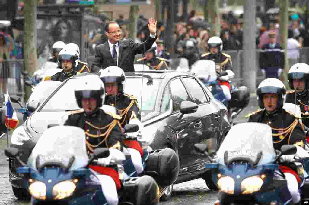 Ông Francois Hollande vẫy chào khi đi qua Ðại lộ Champs Elysees (AP)