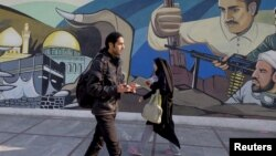 Iranians walk past a revolutionary mural in Tehran, Iran, January 17, 2016.