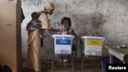 A woman carrying a baby on her back votes in Freetown, Sierra Leone Nov. 17, 2012.