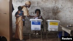 A woman carrying a baby on her back votes at a polling station in Freetown on November 17, 2012.