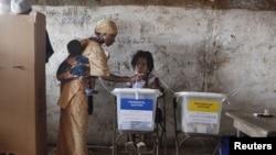 Seorang warga Sierra Leone memasukkan surat suaranya di sebuah TPS di Freetown (17/11).