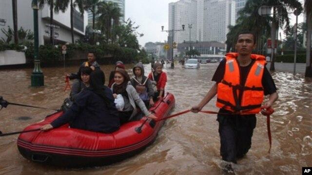 Nhân viên cứu hộ kéo chiếc thuyền cao su đưa cư dân qua một đường phố ngập nước ở Jakarta, ngày 17/1/2013.