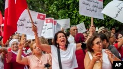 Sejumlah perempuan Tunisia sedang berdemonstrasi menuntut persamaan hak.