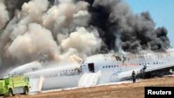 Pesawat Asiana Airlines Boeing 777 diselimuti asap setelah jatuh saat akan mendarat di bandar udara internasional San Francisco di California, 6 Juli. (Reuters/Eugene Anthony Rah)