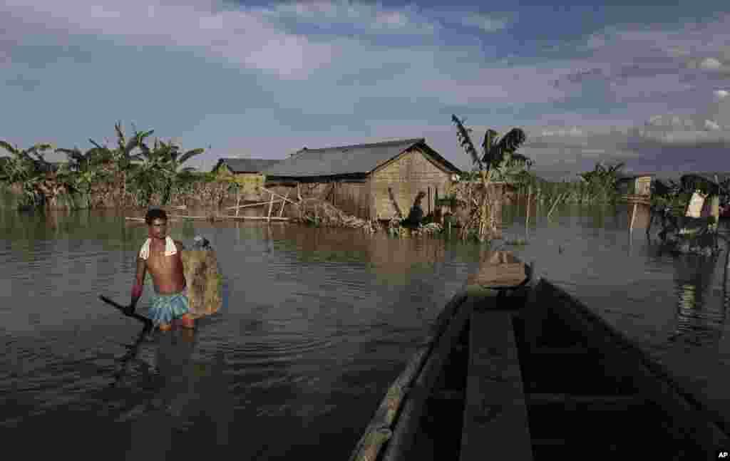 Một dân làng lội qua dòng nước lũ tại làng Gagalmari, bang Assam, ngày 2 tháng 7 năm 2012