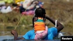 Seorang migran menggendong anaknya ketika menyebrangi sungai Rio Grande di perbatasan AS-Meksiko untuk mencari suaka di wilayah Amerika Serikat pada 22 September 2021. (Foto: Reuters/Daniel Becerril)