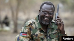 FILE - South Sudan's rebel leader Riek Machar talks on the phone in his field office in a rebel-controlled territory in Jonglei State, South Sudan, Feb. 1, 2014.