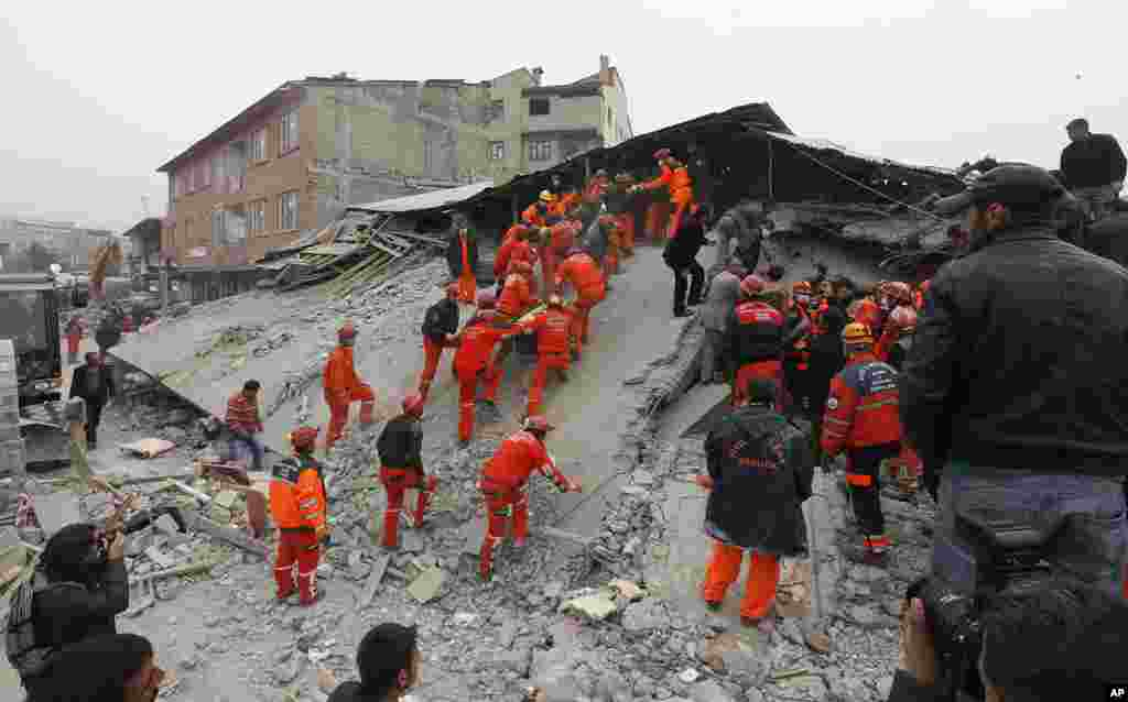 A rescue team carries a generator as they search for survivors under a collapsed building in Ercis, near the eastern Turkish city of Van, October 25, 2011. (Reuters)