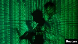 Illustration shows projection of binary code on a man holding a laptop computer, in an office.