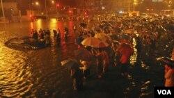 在北京广渠门立交桥附近,救援人员和居民站在一旁观望一辆从街道积水中被拖出的小汽车(7月21日)