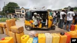 People wait buy kerosene at a petrol station in Lagos, Nigeria, July 4, 2011.