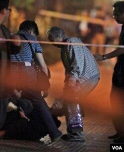 天安门母亲创办人之一丁子霖在北京木樨地儿子被枪杀地点周年祭奠时在她的丈夫蒋培坤(右二)身旁崩溃。他们的儿子蒋捷连在八九六四民主运动期间被戒严解放军开枪打死。(2010年6月3日)