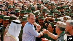 President George H.W. Bush is greeted by Saudi troops and others as he arrives in Dhahran, Saudi Arabia, for a Thanksgiving visit, Nov. 22, 1990. Bush died at the age of 94 on Friday, Nov. 30, 2018, about eight months after the death of his wife, Barbara Bush.