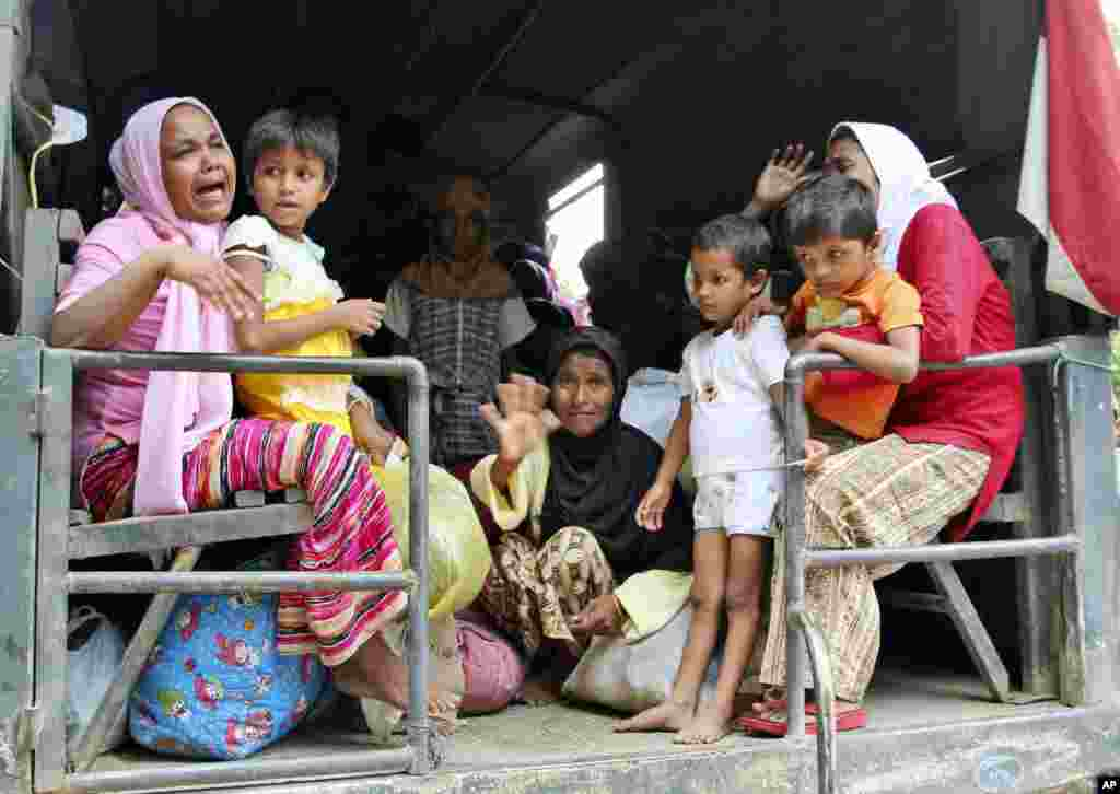 Ethnic Rohingya women and children whose boats were washed ashore on Sumatra Island board a military truck to be taken to a temporary shelter in Seunuddon, Aceh province, Indonesia.