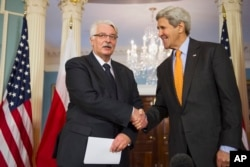 Polish Foreign Minister Witold Waszczykowski shakes hands with Secretary of State John Kerry prior to their meeting at the State Department in Washington, Feb. 17, 2016.
