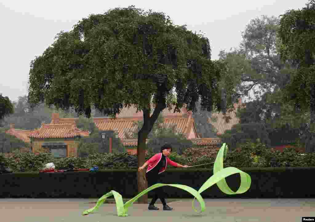 18일 중국 베이징의 경산공원에서 한 여성이 아침체조의 일환으로 리본 운동을 하고 있다.