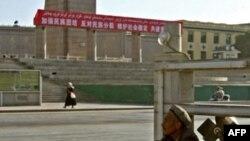 Một người đàn ông Uighur ngồi dưới bức tượng của lãnh tụ Mao Trạch Ðông ở Kashgar