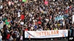 """Ribuan orang menghadiri demonstrasi dengan slogan """"tak terpisahkan"""" melawan kebencian dan untuk solidaritas, bukan pengucilan, di Berlin, Jerman, 13 Oktober 2018. Pengunjuk rasa membentangkan poster bertuliskan """"tak terpisahkan – solidaritas, bukan pengucilan."""" (Foto: AP)"""