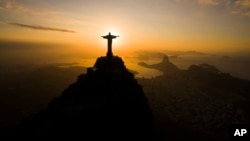 The sun rises behind the Christ the Redeemer statue, above the Guanabara bay in Rio de Janeiro, Brazil, July 19, 2016.