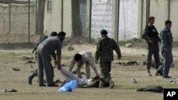 阿富汗警察和便衣安全人員星期一在街上收拾一宗自殺爆炸事件後的屍體