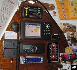 The control panel inside the cabin showing [top, clockwise]: a battery monitor, cart plotter, bilge pump switch panel, stereo, VHF radio and Sea-Me control switches