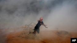 جمعے کے روز مظاہروں کے دوران ایک فلسطینی غزہ کی پٹی میں اسرائیل کی سرحدی باڑ سے ٹکرانے کے بعد گر رہا ہے۔ فضا میں اشک آور گیس کا دھواں نظر آ رہا ہے۔ 5 اکتوبر 2018