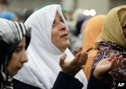 A Muslim woman prays before Muhammad Ali's Jenazah, a traditional Islamic service, at Freedom Hall in Louisville, Ky., June 9, 2016.