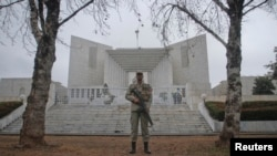 A security official stands guard outside the Supreme Court in Pakistan where PM Gilani was scheduled...