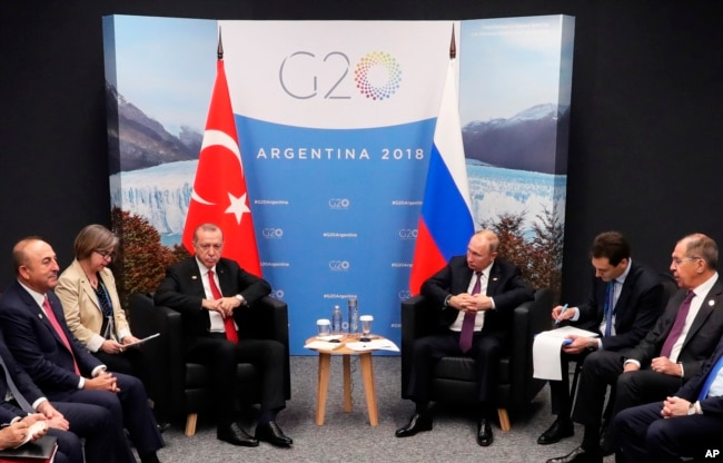 Russian President Vladimir Putin, center right, and Turkey's President Recep Tayyip Erdogan, center left, attend the talks at the G20 summit in Buenos Aires, Argentina, Dec. 1, 2018.